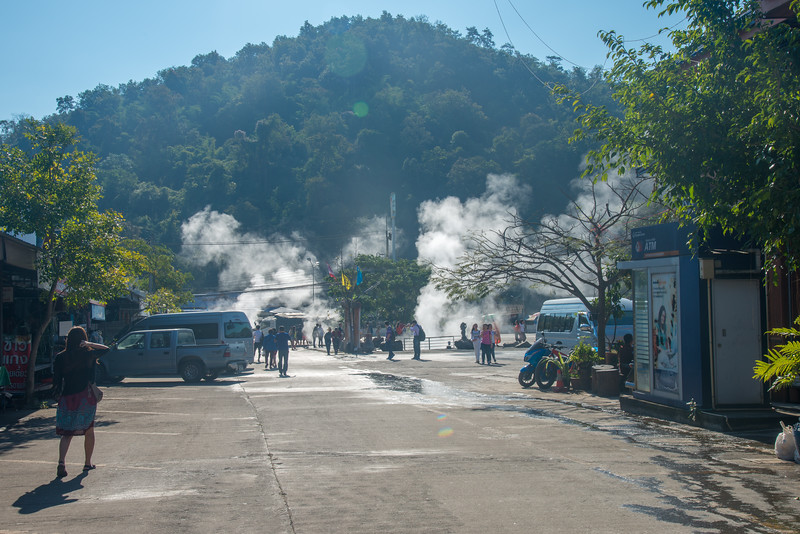Steam coming out at Mae Kachan Hot Spring and Geyser (น้ำพุร้อนแม่ขะจาน เชียงราย) (Wiang Pa Pao) <br /> Maekachan Hot Springs is located in Mae Chedi Mai District, Wiang Pa Pao County, Chiang Rai Province. Has three natural hot spring well. Each pond about 3 meters wide. With temperature of about 80 degrees boiled eggs can be cooked within 3 minutes. You can get rooms with mineral water private bath from the hot springs. Good place to halt between Chiang Mai – Chiang Rai and get a bite or buy souvenirs like clothing, local weaved cotton and jewellery, wood carvings, etc. at the local shop.
