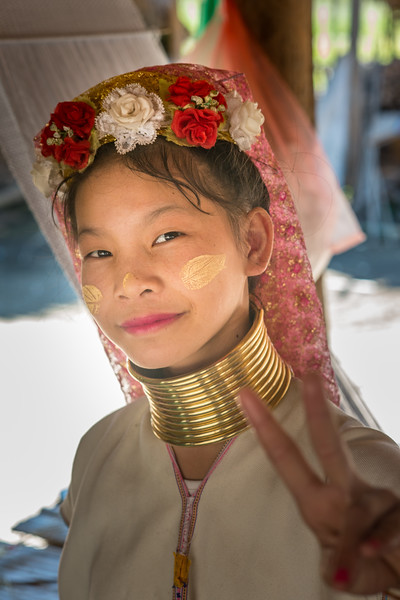 Long Neck Karen in Chiang Rai, Chang Wat Chiang Rai, Thailand<br /> The Karen are a tribal group who have historically lived in the hills on the Myanmar (formerly Burma) side of the Thai border. Best recognized for their elongated necks, the Karen women wear heavy brass rings around their necks, forearms, and shins. There is a lot of criticism surrounding this. From human-zoo to women earning a honest living and not being prosecuted. Depending on which side of the argument you are. When we first arrived each woman was stationed by her own hut busy working on the knitting looms and it initially felt a little bit like a staged atmosphere but talk and spend time and it feels not very different than other villages. Controversy or not, had mixed feelings on this.