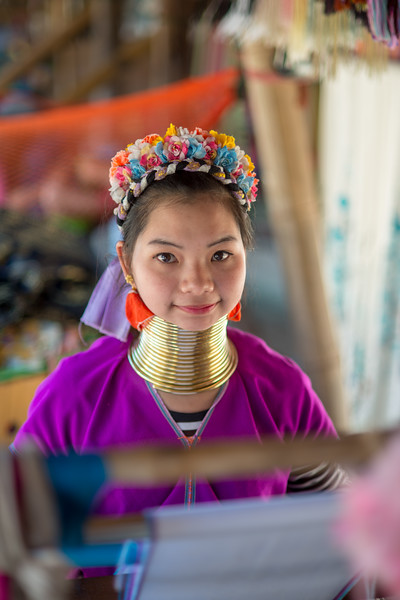 Karen Long Neck girl on the handloom. Long Neck Karen in Chiang Rai, Chang Wat Chiang Rai, Thailand<br /> The Karen are a tribal group who have historically lived in the hills on the Myanmar (formerly Burma) side of the Thai border. Best recognized for their elongated necks, the Karen women wear heavy brass rings around their necks, forearms, and shins. There is a lot of criticism surrounding this. From human-zoo to women earning a honest living and not being prosecuted. Depending on which side of the argument you are. When we first arrived each woman was stationed by her own hut busy working on the knitting looms and it initially felt a little bit like a staged atmosphere but talk and spend time and it feels not very different than other villages. Controversy or not, had mixed feelings on this.