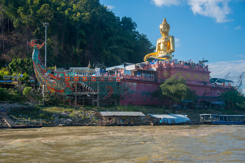 Golden Triangle Buddha Temple on the Thai side of the Mekong River in Chiang Saen District, Chiang Rai, Thailand. Across the river is Laos and the Golden Triangle Special Economic Zone (SEZ).