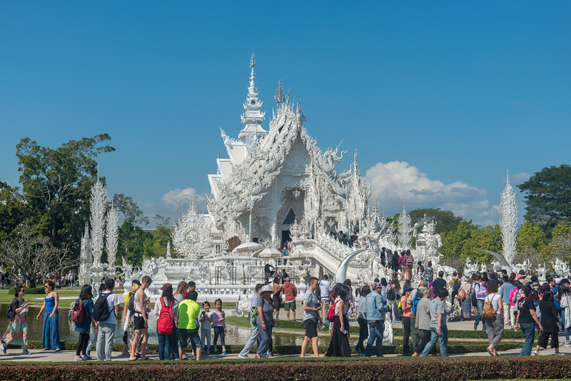 Very large crowds visit Wat Rong Khun White Temple (วัดร่องขุ่น) <br /> Contemporary Buddhist temple drawing massive crowds with its unique, intricate white exterior. Wat Rong Khun, also known as the White Temple, is a contemporary, unconventional, privately-owned art exhibit in the style of a Buddhist temple in Chiang Rai Province, Thailand.