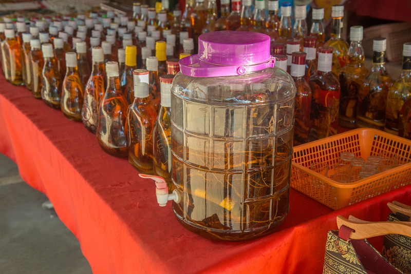 Snake whiskey including free tasting from the jar of the snake/scorpion/roots dunked whiskey at Don Sao, Laos. <br /> <br /> Across the Mekong River from Northern Thailand is Don Sao, Laos. The Golden Triangle is where Thailand, Myanmar and Laos meet on the mighty Mekong River. Historically this area was well known for opium trade on the no-man-island between these three countries. The river enabled opium to be transported from Myanmar and Thailand to China and Southern Southeast Asia.