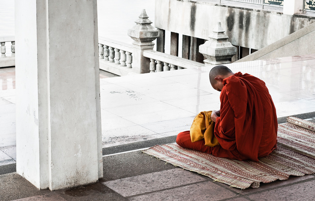 Buddhist monk meditating by the Mekong River.<br /> <br /> Nong Khai, Thailand, 2010.