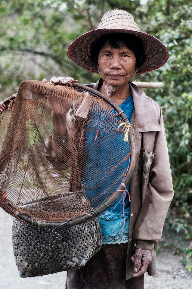 Local woman from a small hamlet returning home with her daily catch of small fish.<br /> <br /> Northern Thailand, 2010.