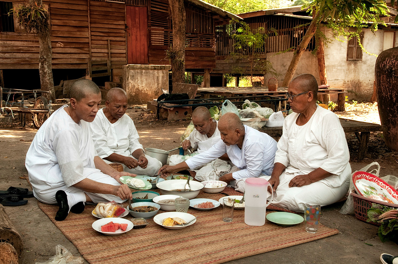 Lay followers having lunch, usually consisting of noodle soup, rice and fruit. <br /> <br /> Northern Thailand, 2010.