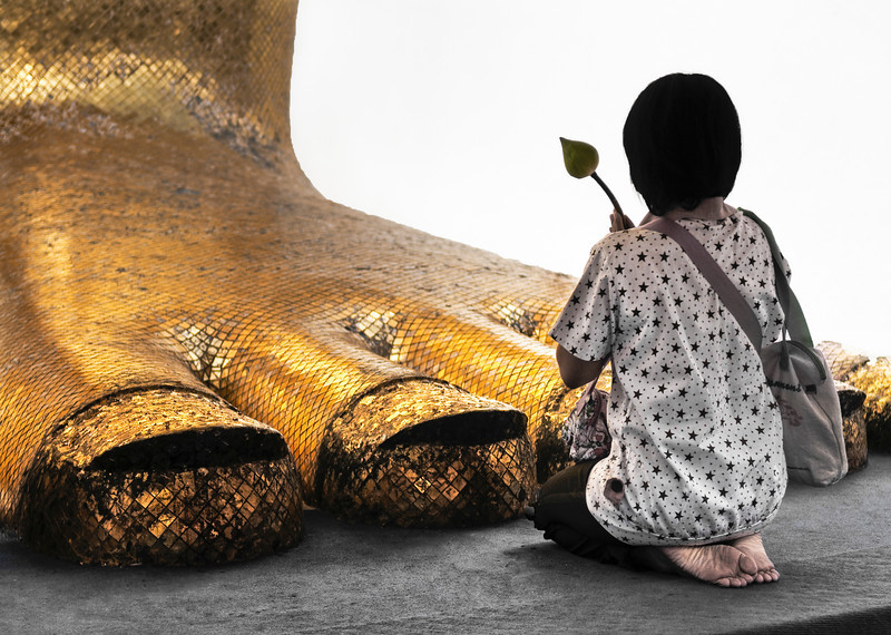 Woman prying at the feet of a 32.5m, standing Buddha referred to as Luang Pho To or Phrasiariyametri. It took over 60 years to complete and is decorated in glass mosaics and 24-carat gold.<br /> <br /> Wat Intharawihan, Bangkok, Thailand, 2010.