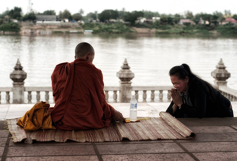 Woman prying to a Monk by the Mekong River, after having given him a bottle of water. <br /> <br /> Nong Khai, Thailand, 2010.