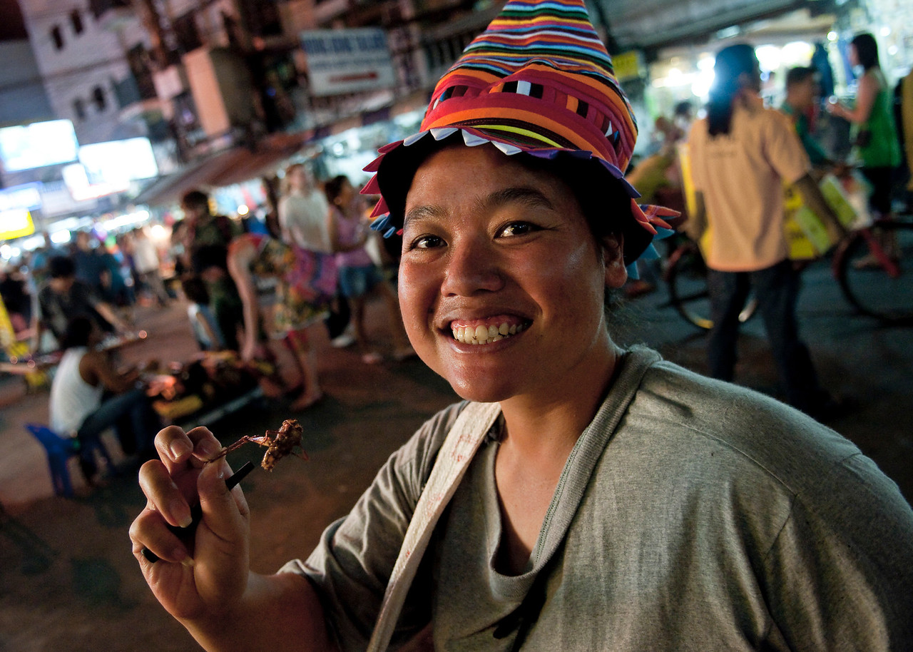 woman eating grasshopper.<br /> <br /> Bangkok, 2010.