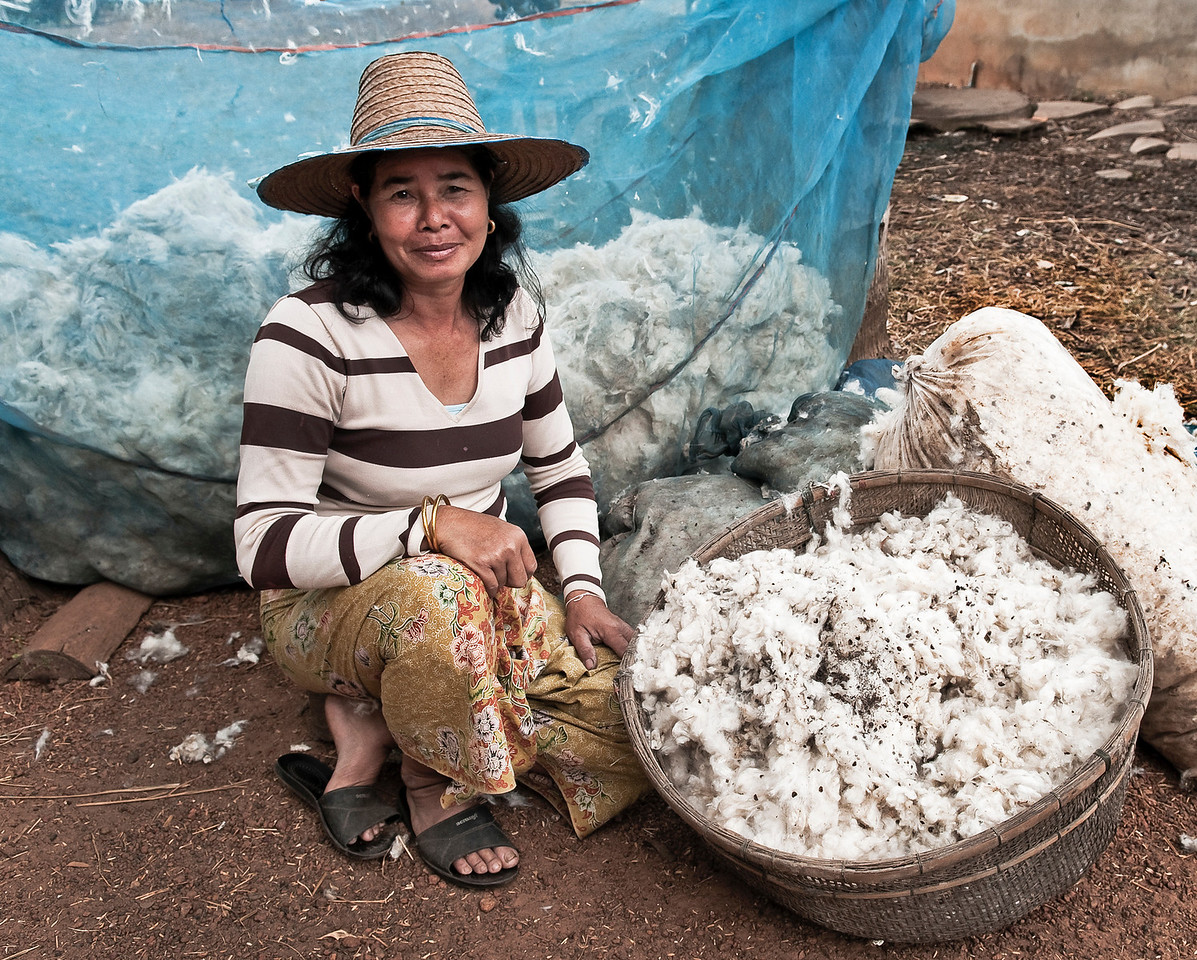 Farmer packing wool into sacks ready to be taken to the local consortium.<br /> <br /> Northern Thailand, 2010.