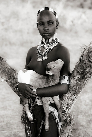 This is Teri, a young girl from the Hamar tribe.  Teri is not yet married, evident as she does not support the hairstyle of little dreadlocks of a married woman. Wife beating is an accepted part of life rather than a taboo, and the convention is that a man will not generally tell his wife why she is being whipped. On the other hand, if a beating is severe then family or neighbours will step in. After the couple have had two or three children, the beating stops.  Omo Valley, Southern Ethiopia, 2013.