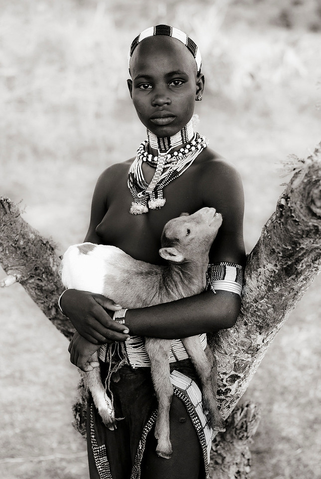 This is Teri, a young girl from the Hamar tribe. <br /> Teri is not yet married, evident as she does not support the hairstyle of little dreadlocks of a married woman. Wife beating is an accepted part of life rather than a taboo, and the convention is that a man will not generally tell his wife why she is being whipped. On the other hand, if a beating is severe then family or neighbours will step in. After the couple have had two or three children, the beating stops.<br /> <br /> Omo Valley, Southern Ethiopia, 2013.