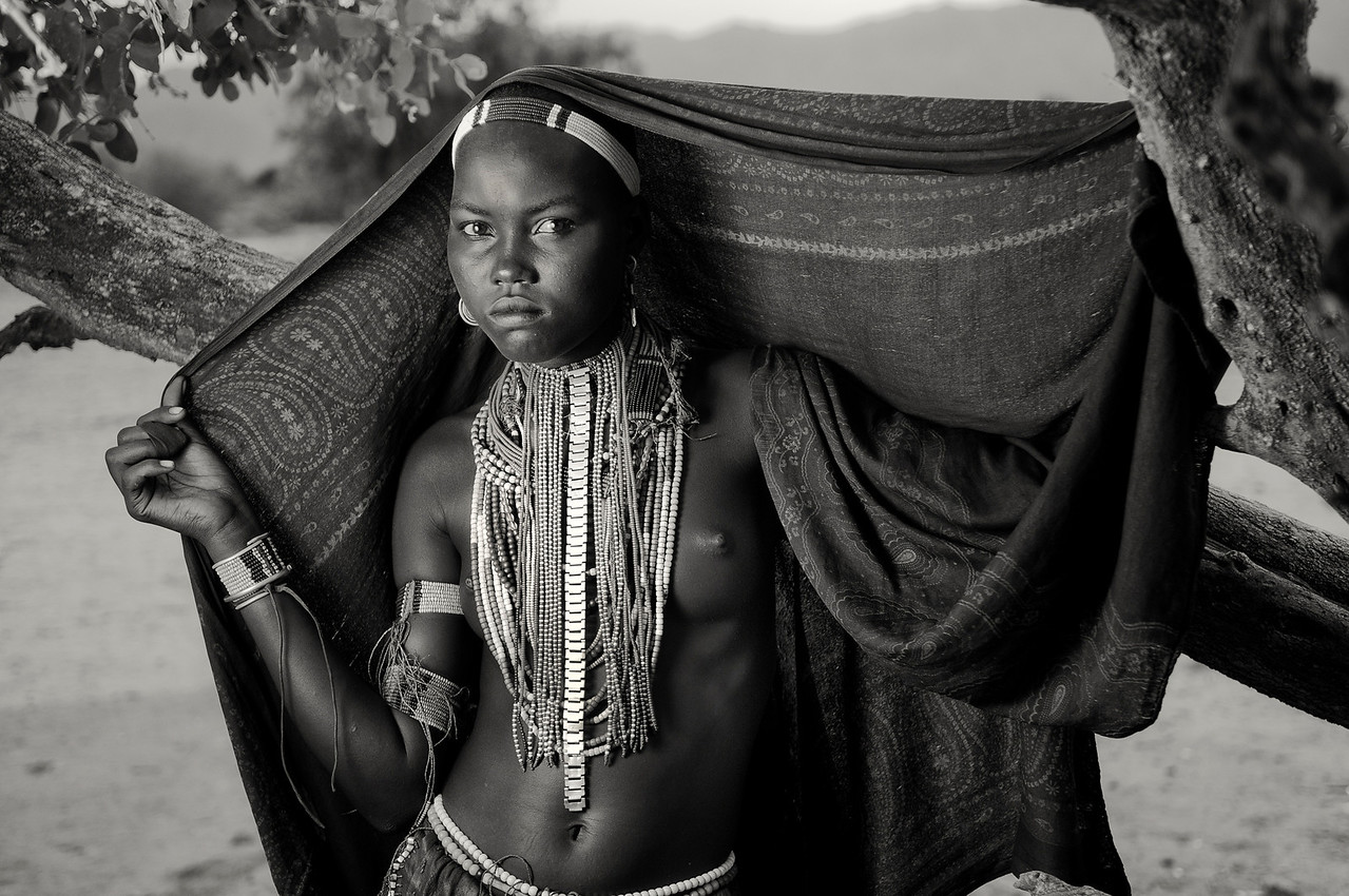 This is Selasoti, a young Arbore virgin. The Arbore People whose primary religion is Islam, are from the Omotic language family and live in Southern Ethiopia, south-west of the Omo Valley. Konso is the lingua franca in this area. They have ancestral and cultural links to the Konso people and perform many ritual dances while singing. The Tsemay people are their neighbouring tribe. Arbore people are pastoralists (livestock farmers). They believe that their singing and dancing eliminates negative energy and with the negative energy gone, the tribe will prosper.<br /> <br /> Omo Valley, Southern Ethiopia, 2013.
