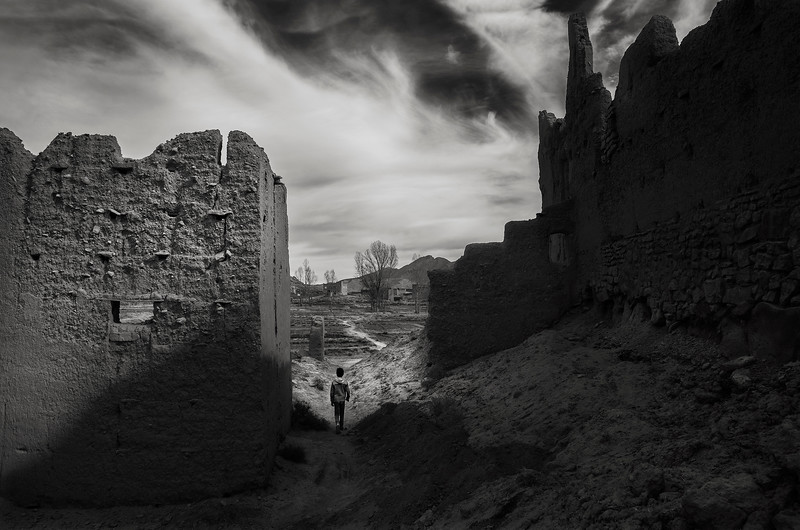 A young boy walking past the ruins of an old Ksar.  Tamtetoucht, Morocco, 2018