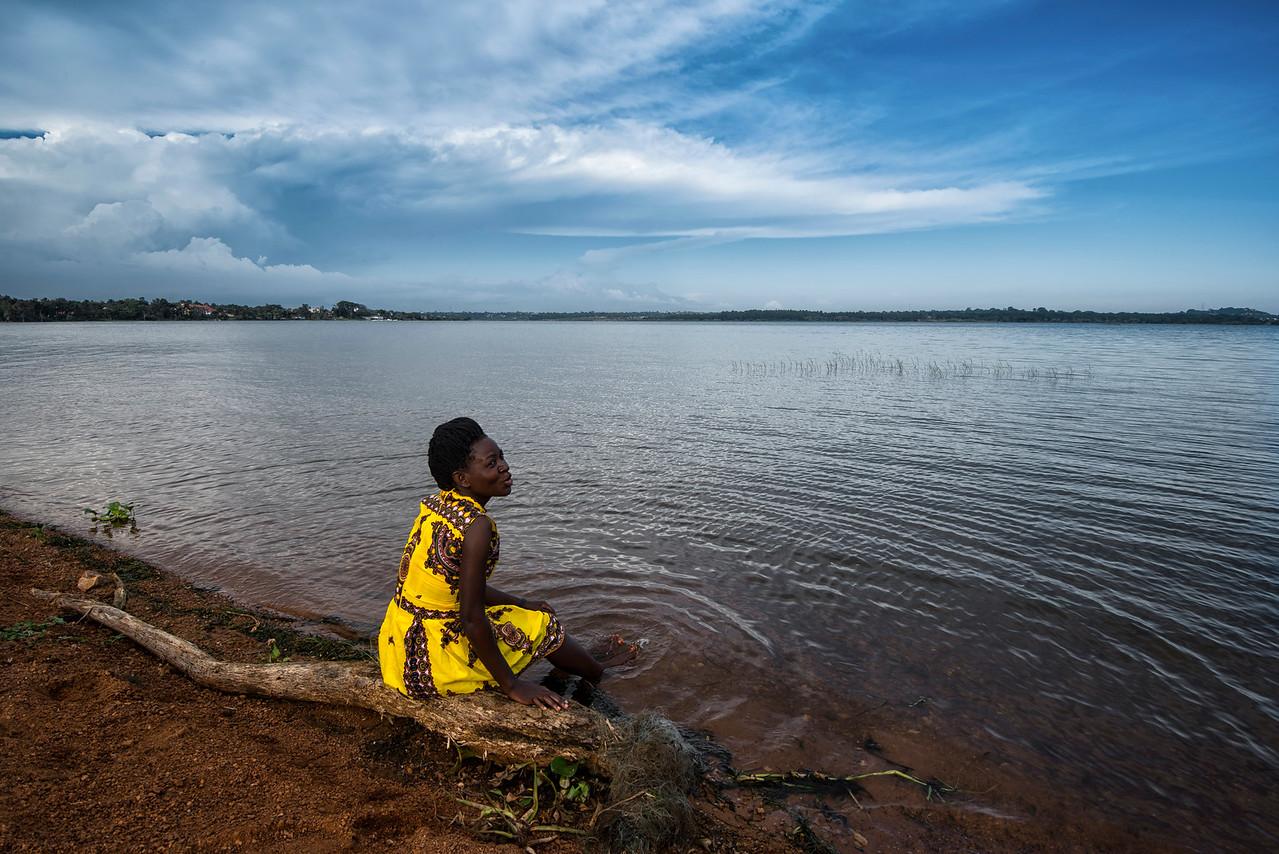 Woman sitting on the shores of lake Victoria, Uganda, 2016.