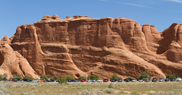"""Parking lot at Devil's Garden trailhead, Arches National Park.  Cf. Edward Abbey:  """"No more cars in national parks. Let the people walk. Or ride horses, bicycles, mules, wild pigs--anything--but keep the automobiles and the motorcycles and all their motorized relatives out. We have agreed not to drive our automobiles into cathedrals, concert halls, art museums, legislative assemblies, private bedrooms and the other sanctums of our culture; we should treat our national parks with the same deference, for they, too, are holy places."""" ― Edward Abbey, Desert Solitaire"""
