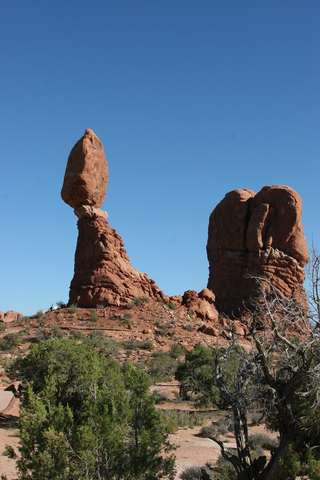 Balanced Rock in Arches National Park.  Hardened slickrock (petrified sandstone) above, softer mudstone below.  The mudstone erodes faster, and soon this enormous rock will come tumbling down.
