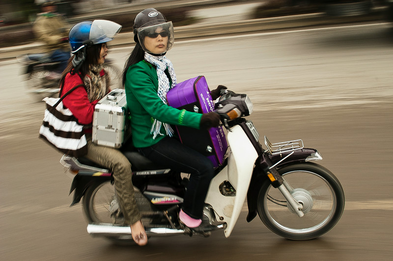 Two young women on a moped.<br /> <br /> Saigon, Vietnam, 2008.