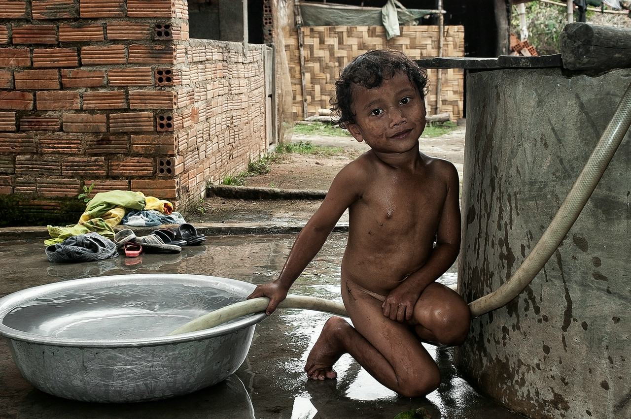 Mnong boy washing  in a Jun Village.<br /> <br /> Vietnam, 2008