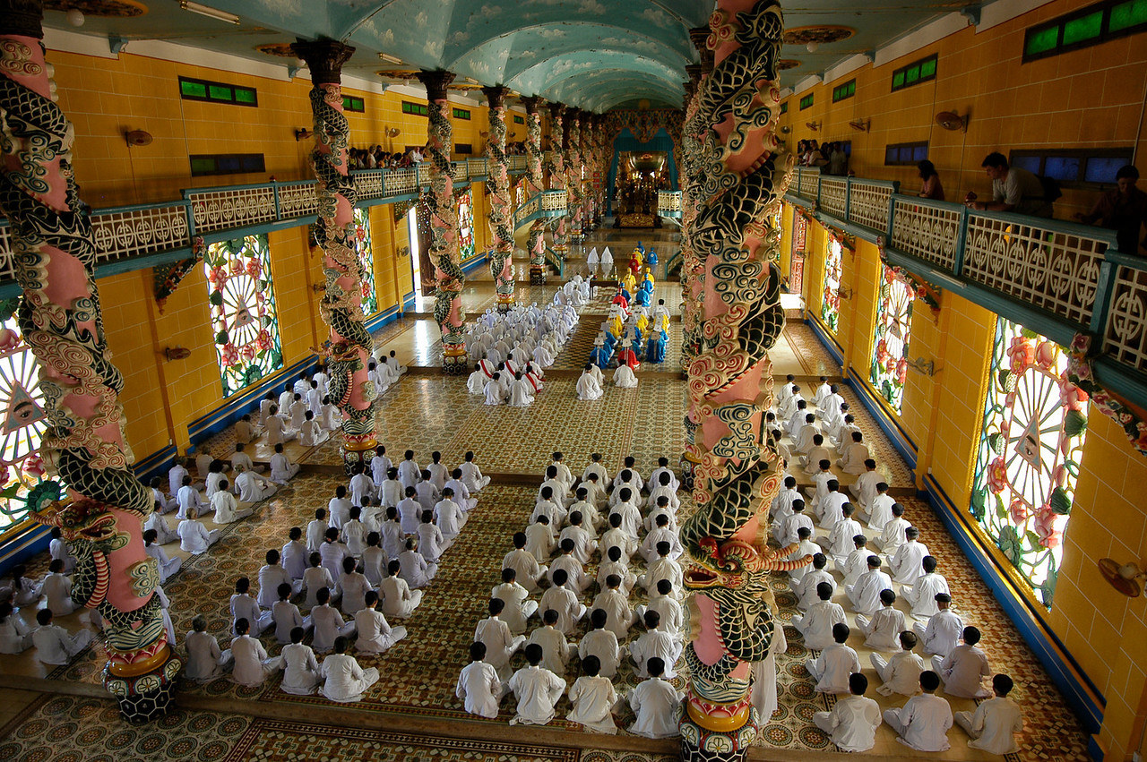 Worshipers at the Cao Dai great Temple. Adherents engage in ethical practices such as prayer, veneration of ancestors, nonviolence, and vegetarianism with the minimum goal of rejoining God the Father in Heaven and the ultimate goal of freedom from the cycle of birth and death.  <br /> <br /> Tay Ninh, North of Saigon, Vietnam, 2008