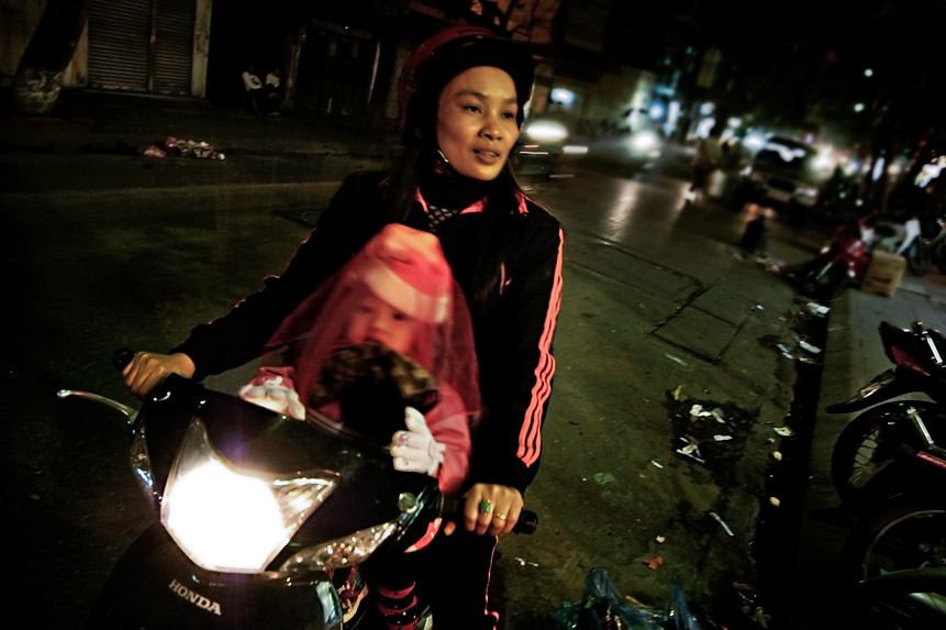 Mother and child riding a moped on a back street.<br /> <br /> Hanoi, Vietnam, 2008