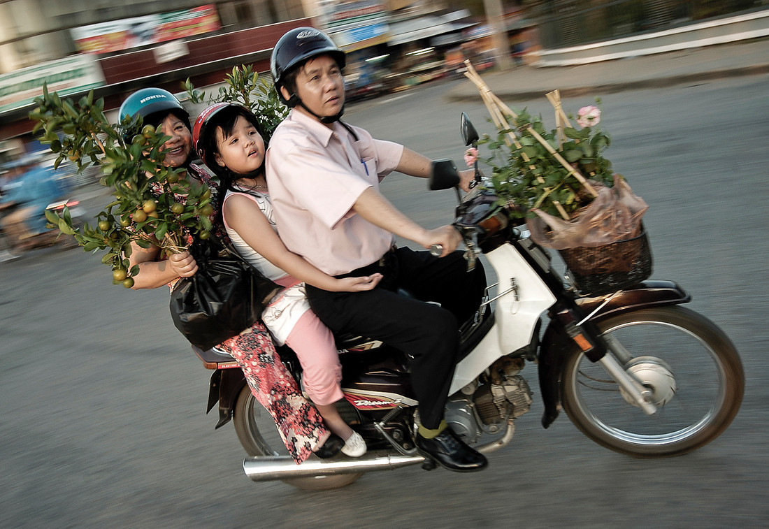 Family going shopping on there moped. Mopeds are everywhere in Vietnam. In a country were cars are a luxury that only a very small minority can afford, mopeds have become a status symbol. <br /> <br /> Rach Gia, Vietnam, 2008
