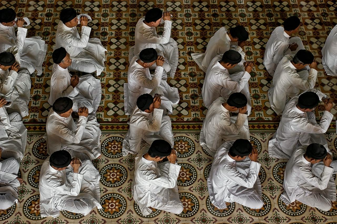 Worshipers deep in prayer at the Cao Dai great Temple at Tay Ninh.<br /> <br /> North of Saigon, Vietnam, 2008