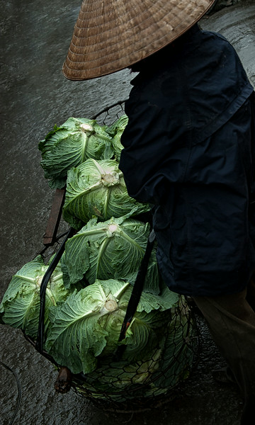Farmer selling cabbages at the local street market.  Ninh Binh, Vietnam, 2008