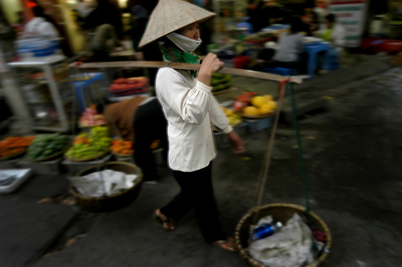 Woman carrying her shopping the traditional way.<br /> <br /> Hanoi, Vietnam, 2008