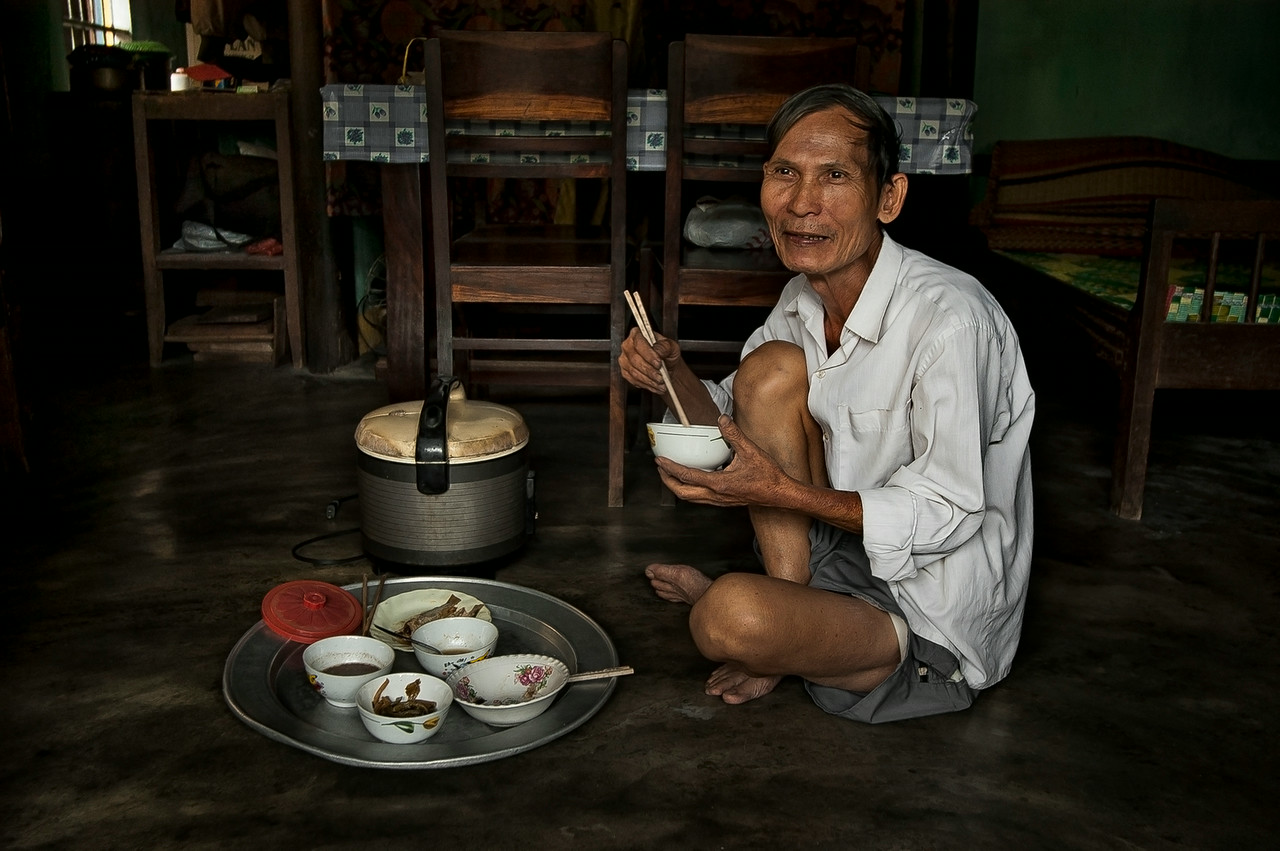 Although many homes have chairs and tables, most still prefer to eat the traditional way by sitting on the floor. <br /> <br /> Hoi An, Vietnam, 2008