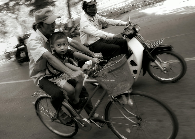 Young boy riding with his father. In Vietnam, preventable road accidents are the cause of more than 10,000 deaths every year.<br /> <br /> Saigon, Vietnam, 2008