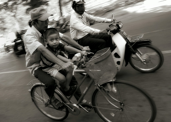 Young boy riding with his father. In Vietnam, preventable road accidents are the cause of more than 10,000 deaths every year.  Saigon, Vietnam, 2008