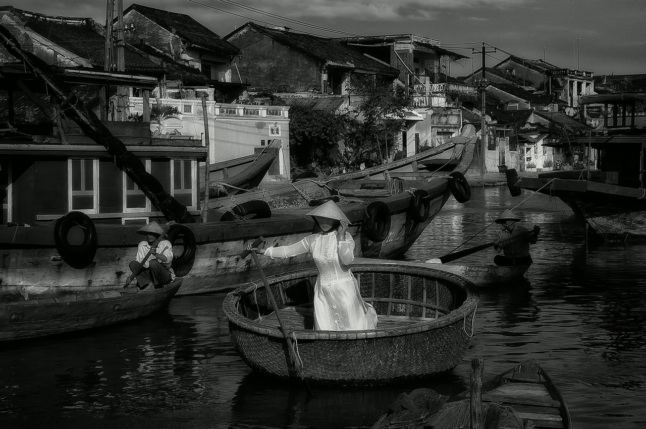 Woman rowing on a traditional sampan, <br /> <br /> Hoi An, Vietnam, 2008.