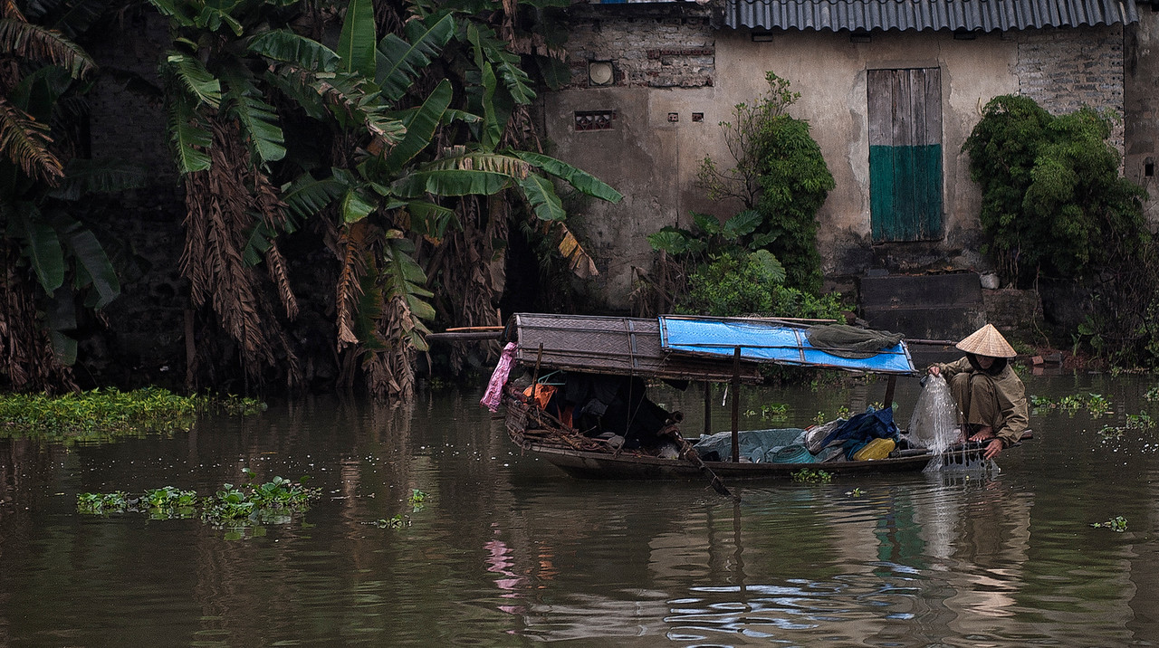 woman fishing in a river.<br /> <br /> Vietnam, 2008.