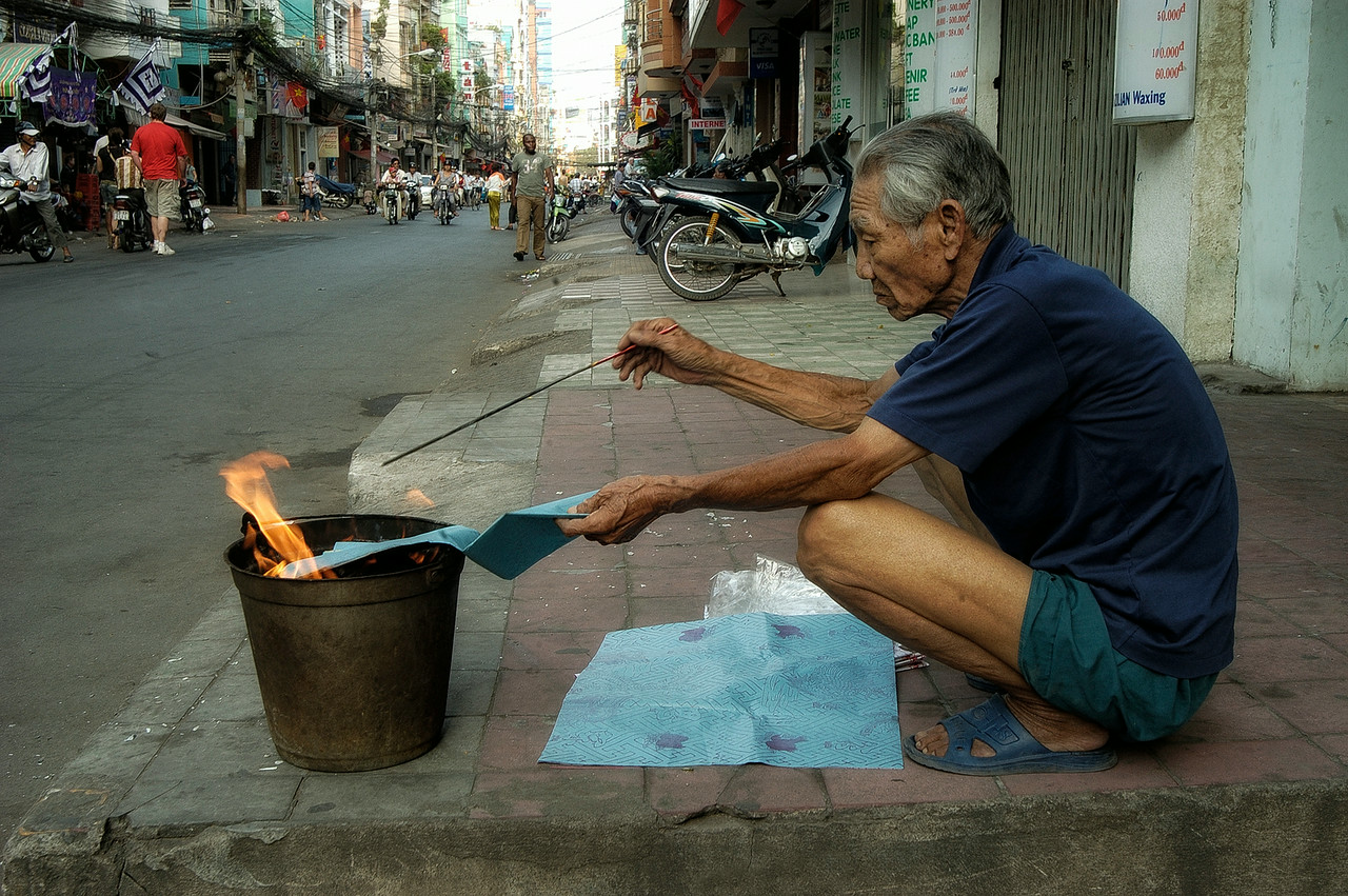 """Tết Trung Nguyên, This festival is viewed as the time for the pardoning of condemned souls who are then released from hell.The """"homeless"""" should be """"fed"""" and appeased with offerings of food. Merits for the living are also earned by the release of birds and fish. This man can be seen burning paper money as an offering to the souls.<br /> <br />  Saigon, Vietnam 2008"""