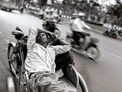 Rickshaw driver takes an afternoon nap in a busy Saigon Street.   Saigon, Vietnam, 2008