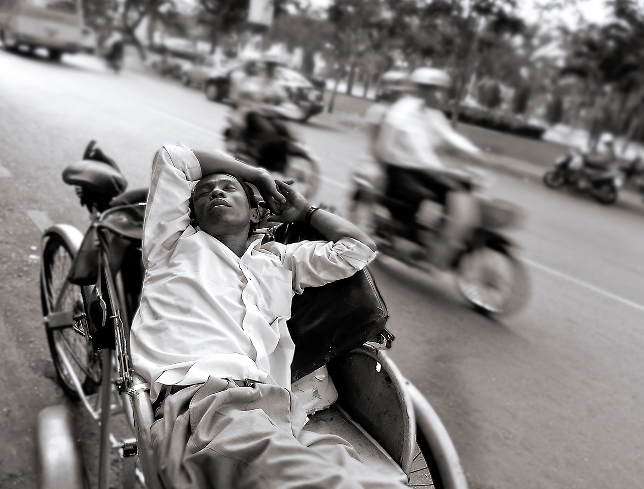 Rickshaw driver takes an afternoon nap in a busy Saigon Street. <br /> <br /> Saigon, Vietnam, 2008