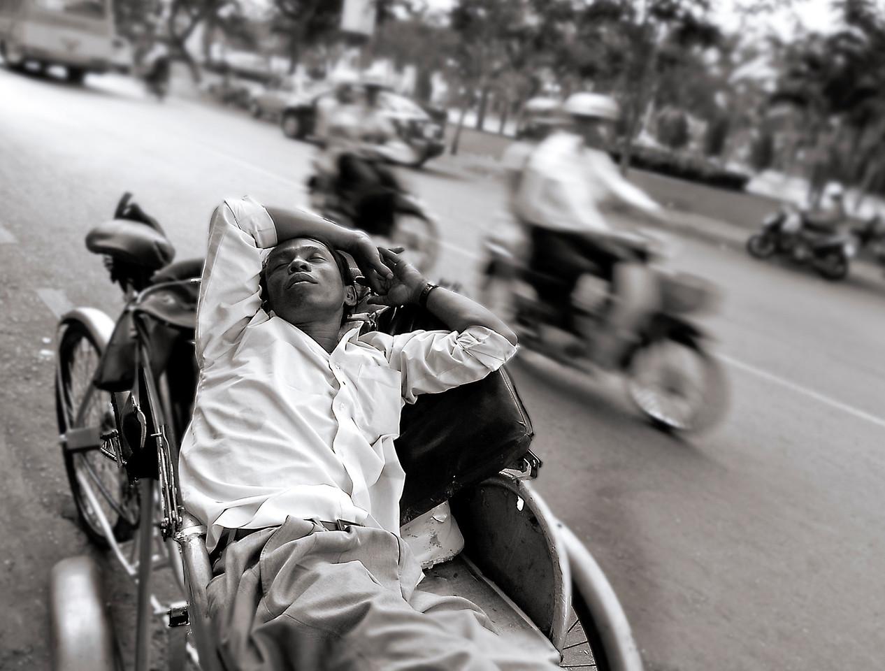 Rickshaw driver takes an afternoon nap in a busy Saigon Street. <br /> <br /> Saigon, Vietnam, 2008
