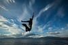 Person jumping above lake, Yukon
