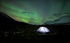 Lit up tent under the aurora borealis, Tombstone Territorial Park, Yukon, Canada.