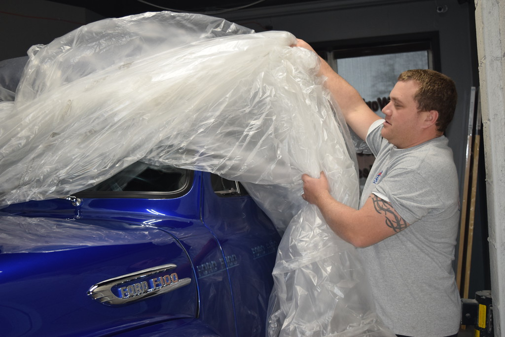 . Eric Lafata of St. Clair Shores and co-owner of Lafata Auto Body in Roseville peels the plastic back to reveal one of several cars he will be showcasing at the 2018 Detroit Autorama. GINA JOSEPH - THE MACOMB DAILY