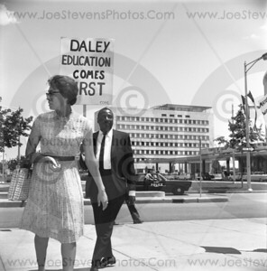 Dick Gregory marching with his sign in hand showing his interest in education coming first evidentally before politics, financial planning or segregation.  Here in 1965 Dick Gregory takes issue with Chicago's Mayor Daley not putting education as a top priority.