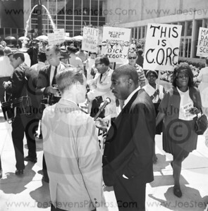 "Civil Rights Activist, Dick Gregory in 1965 Downtown Detroit beside Cobo Hall being interviewed by a local Detroit TV News Caster.  The activist group named ""CORE"" were leading this march along with Mr. Gregory in his support and in their struggle for equal rights, equal housing & better education  & sounding off for Chicago's Mayor Daley.to act on these issues in a time of black uprising and awareness.  Times would get worse before they got better in Detroit until the riots of 1967 which led President Johnson to note the cause of black rioting throughout major cities was because blacks & whites were living in ""Two Societies"".  To the average American & the lone citizen, the awareness of a new world and letting go of past suppression needed to be brought into the mainstream.  Dick Gregory would put his neck out and do what he had to, to bring attention to this awareness."