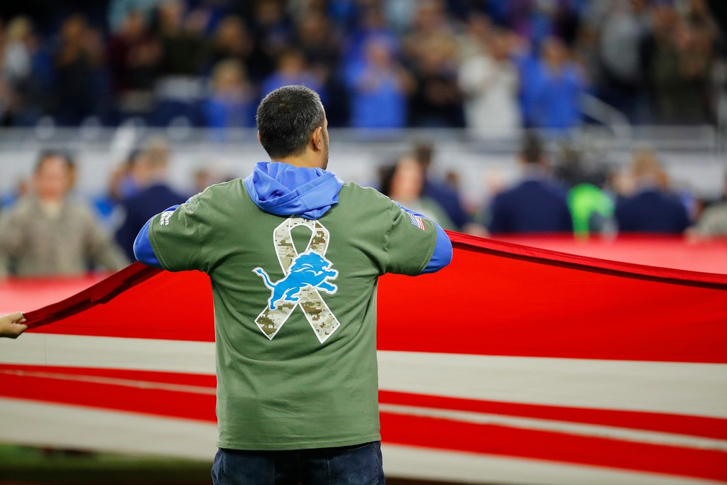 . A Detroit Lions fan helps hold the flag during the national anthem before the first half of an NFL football game between the Detroit Lions and the Cleveland Browns, Sunday, Nov. 12, 2017, in Detroit. (AP Photo/Rick Osentoski)
