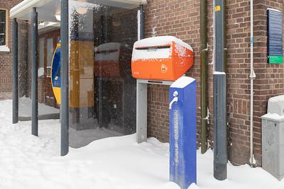 Oranje PostNL brievenbus in de sneeuw