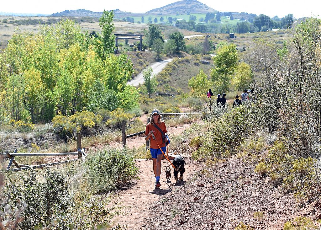 . Debbie Bendell of Loveland walks her dogs, Ed, center, and Jennie, along a trail Friday, Sept. 21, 2018, at the Devil\'s Backbone Open Space in Loveland.  (Photo by Jenny Sparks/Loveland Reporter-Herald)