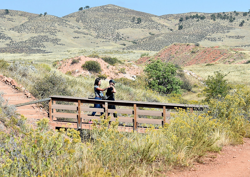 Bennett Balcer holds his wife, Brittney Balcer's hand as they cross a bridge Friday, Sept. 21, 2018, at the Devil's Backbone Open Space in Loveland.  (Photo by Jenny Sparks/Loveland Reporter-Herald)