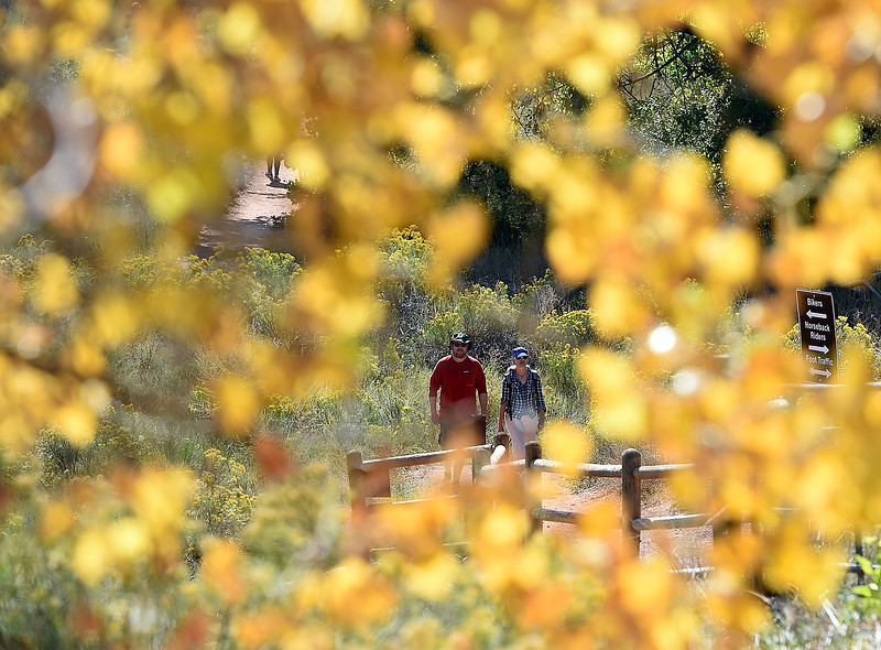 Shannon Phelps, left, and Molly McLean are framed leaves changing color as they hike Friday, Sept. 21, 2018, at the Devil's Backbone Open Space in Loveland.  (Photo by Jenny Sparks/Loveland Reporter-Herald)