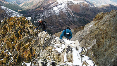 The white band of rock is quartzlike material. There is a narrow ledge to the right. Beyond that is a 2,400' drop to Kane Creek.