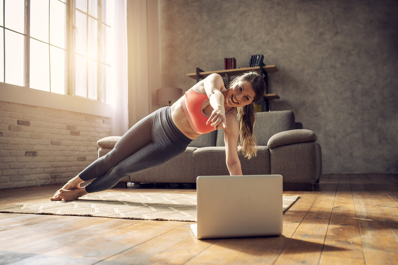 Young girl follows with a laptop a gym exercises. She is at home due to coronavirus codiv-19 quarantine