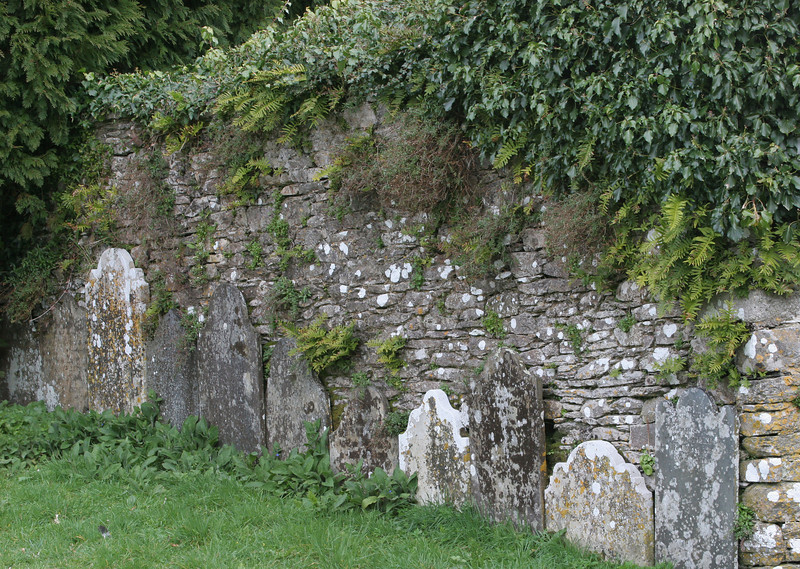 Some of the headstones are set against one of the older walls.